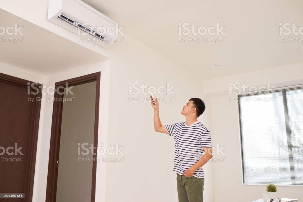 Portrait Of Happy Man Using Remote Control To Operate Air Conditioner stock photo