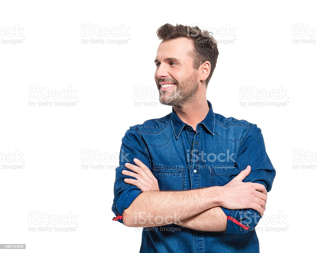 Portrait of happy man wearing jeans shirt Portrait of happy adult man wearing jeans shirt, standing against the white background with arms crossed, looking away.  2015 Stock Photo