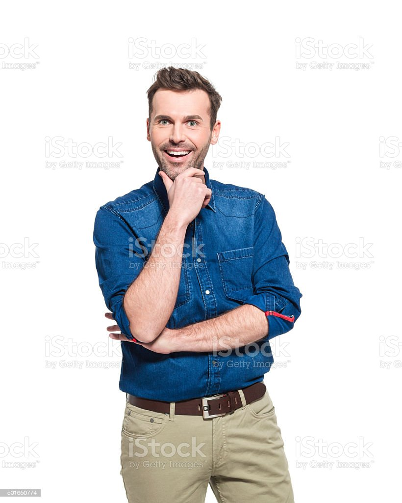 Portrait of happy man wearing jeans shirt Portrait of happy adult man wearing jeans shirt, standing against the white background with hand on chin, smiling at camera. 30-39 Years Stock Photo