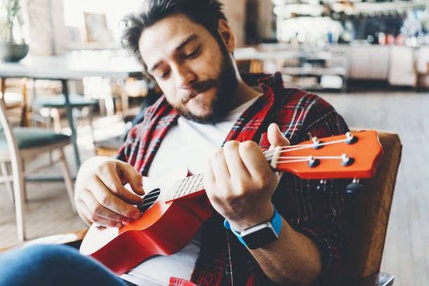 Portrait of happy man with flannel shirt playing ukulele in big room stock photo