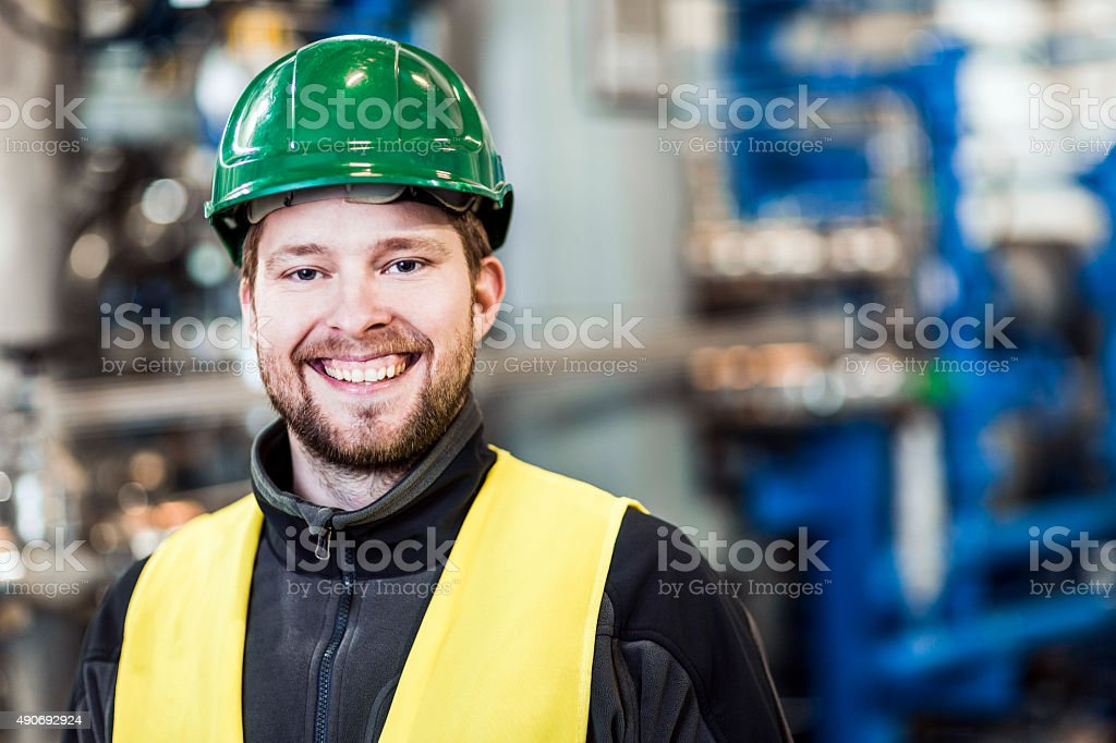 Portrait of happy manual worker at factory stock photo