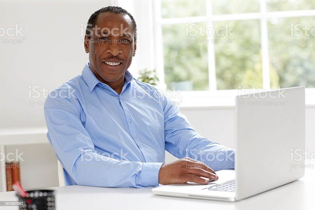 Portrait of happy mature African businessman at work stock photo