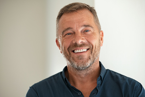 Handsome businessman smiling and looking at camera. Portrait of carefree mature man with copy space. Successful mid adult business man laughing.