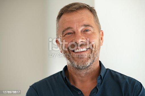 istock Portrait of happy mature man smiling 1278978817