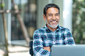 istock Portrait of happy mature man with white, grey stylish short beard looking at camera outdoor. Casual lifestyle of retired hispanic people or adult asian man smile with confident at coffee shop cafe. 1089952014