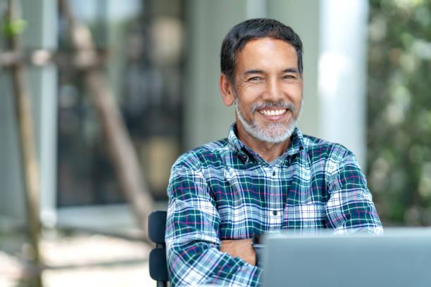 幸福成熟男人的肖像與白色, 灰色時尚的短鬍子看著鏡頭戶外。退休的西班牙裔或亞洲成年人的隨意生活方式在咖啡店的咖啡館裡自信地微笑。 - 亞洲 個照片及圖片檔