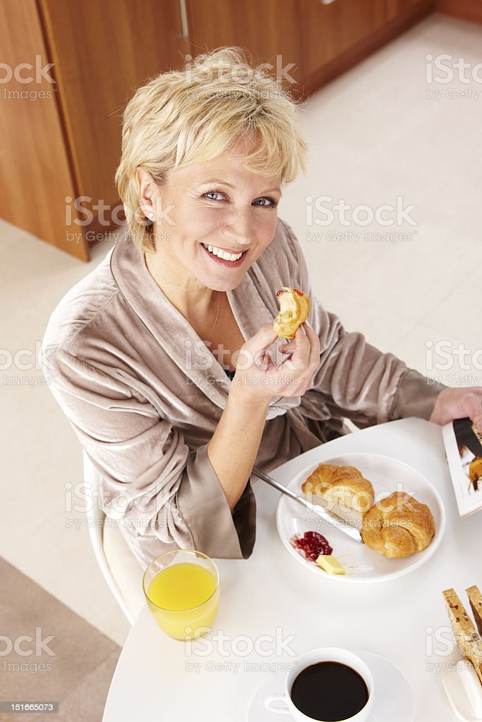 Portrait of happy mature woman having breakfast at home royalty-free stock photo