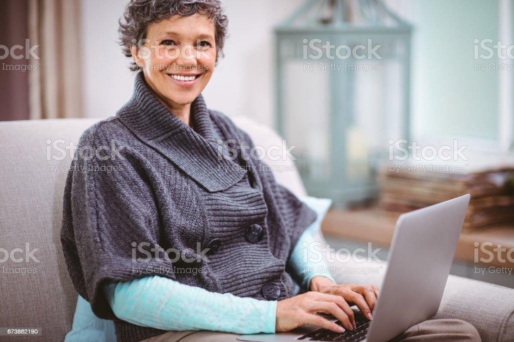 Portrait de femme d'âge mûr heureuse à l'aide d'ordinateur portable photo libre de droits