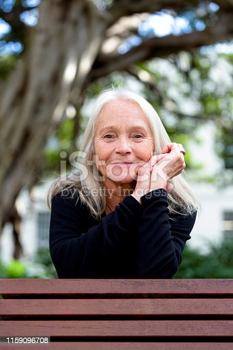 Portrait of happy senior woman with hands on chin, background with copy space, full frame horizontal composition