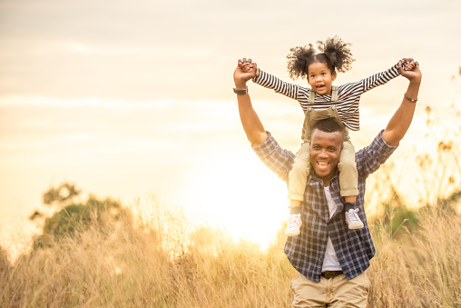 Portrait of Happy Mixed race African family little child girl sitting on her father neck while hiking on the mountain at sunset with smiling face. Parent and kid enjoy and having fun in summer vacation