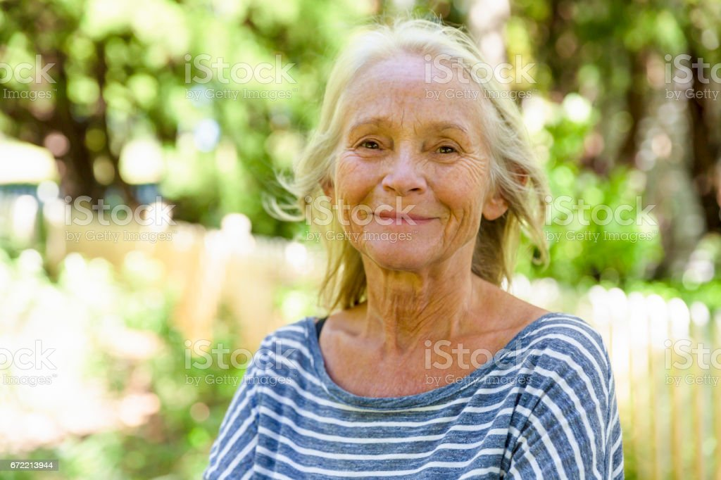 Portrait of happy, modern, attractive mature woman in sunshine stock photo
