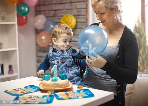 istock portrait of happy mom and baby with birthday cake 502726908