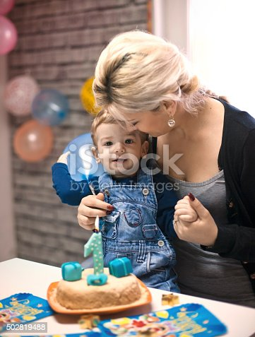 istock portrait of happy mom and baby with birthday cake 502819488
