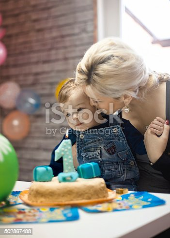 istock portrait of happy mom and baby with birthday cake 502867488