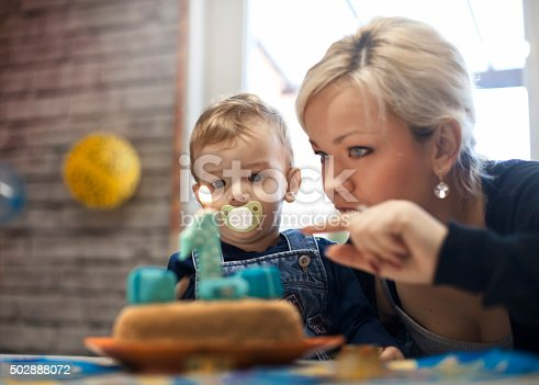 istock portrait of happy mom and baby with birthday cake 502888072