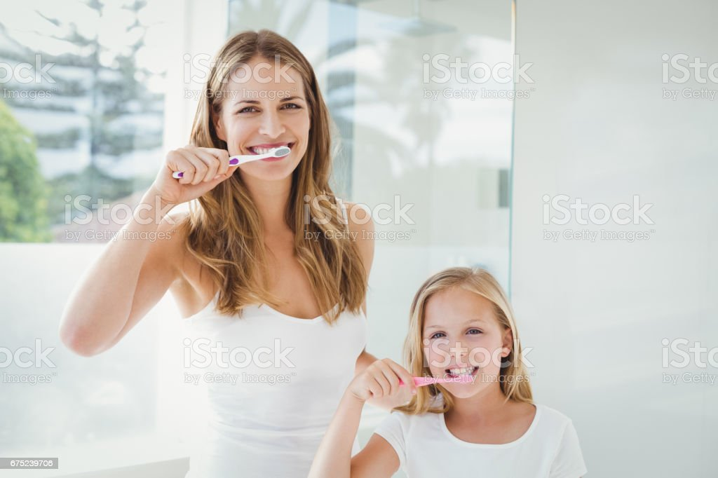 Portrait of happy mother and daughter brushing teeth royalty-free stock photo