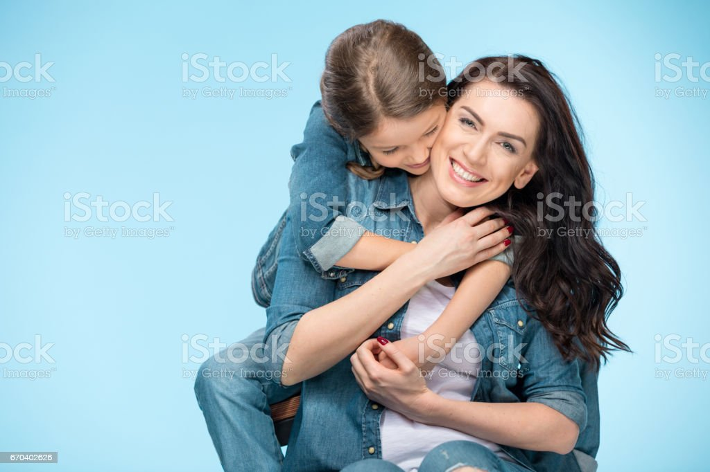 portrait of happy mother and daughter hugging in studio on blue stock photo