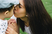 istock Portrait of happy mother kissing her son outdoors 614953778