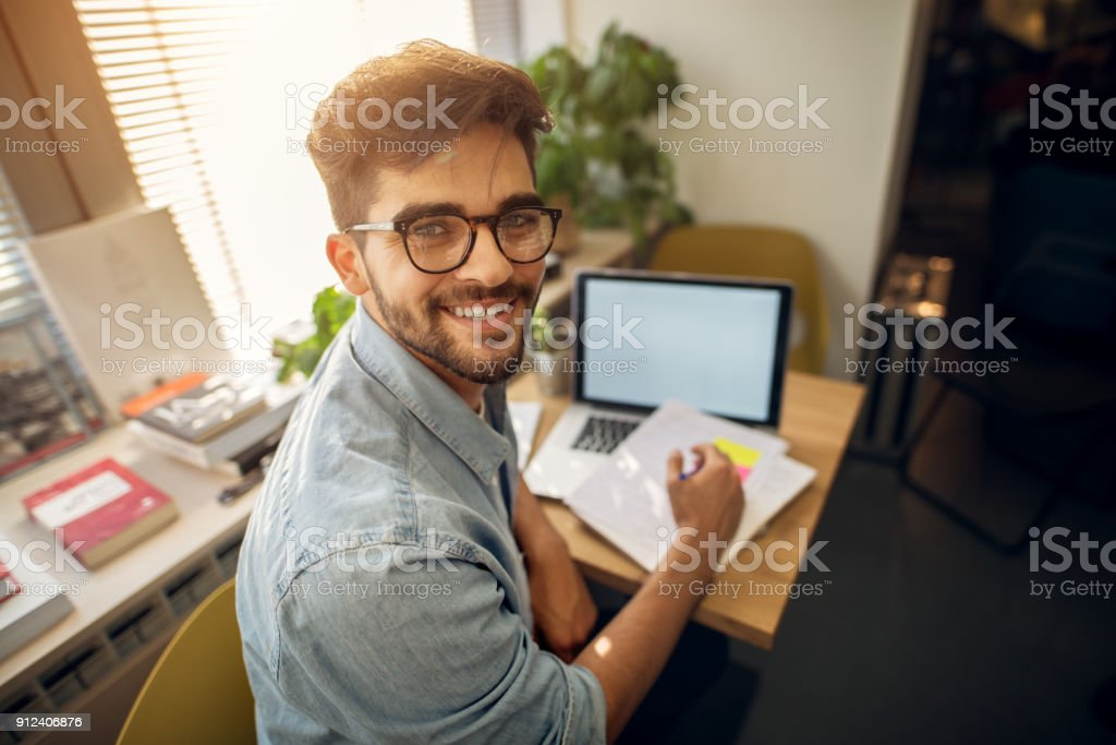 Portrait of happy motivated smiling hipster student learning for a test or an exam at high school library desk while sitting turn backwards and looking at the camera. stock photo