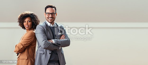 Portrait of cheerful multi ethnic business couple wearing suit and looking at camera with lot of copy space on right side