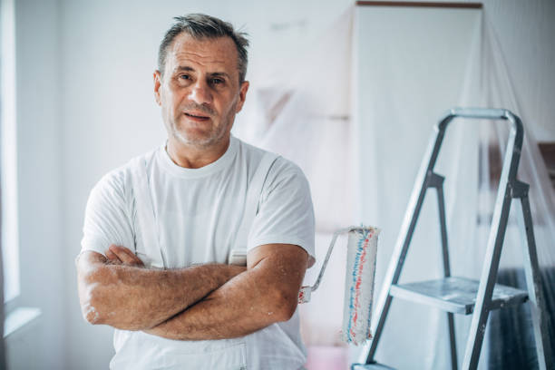 Portrait of happy painter Painter standing with crossed arms in the living room eastern europe stock pictures, royalty-free photos & images