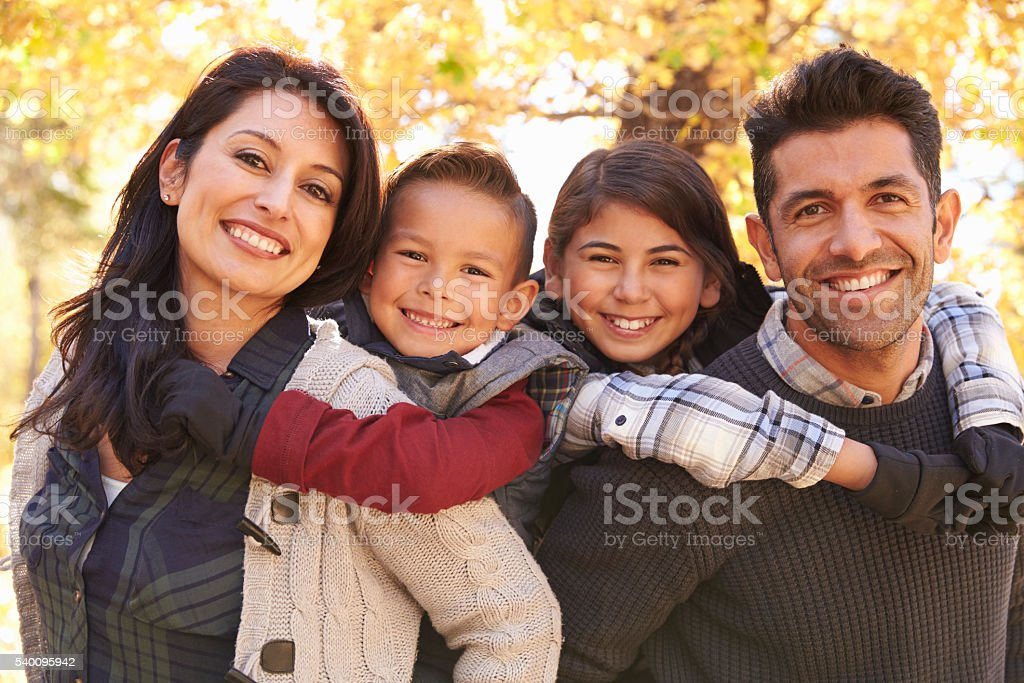 Portrait of happy parents piggybacking kids outdoors stock photo