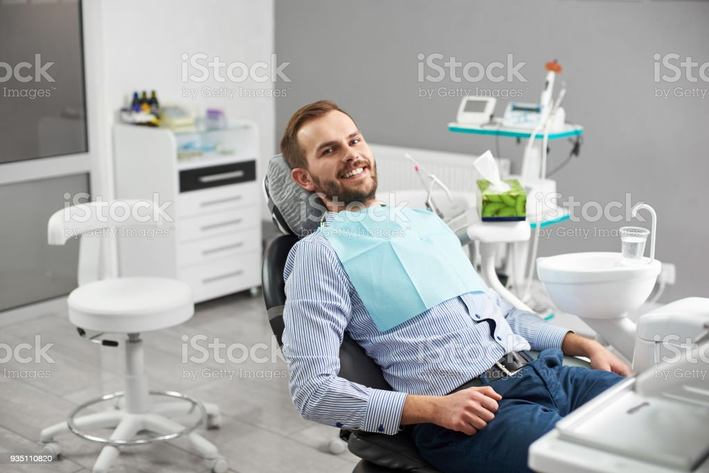 Portrait of happy patient in dental chair. Modern dentistry with the use of new technologies stock photo