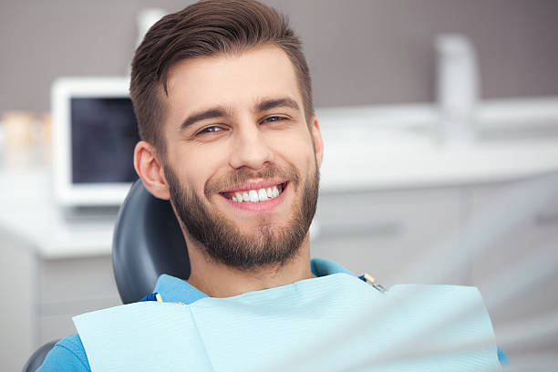 portrait of happy patient in dental chair. - zahnarzt stock-fotos und bilder