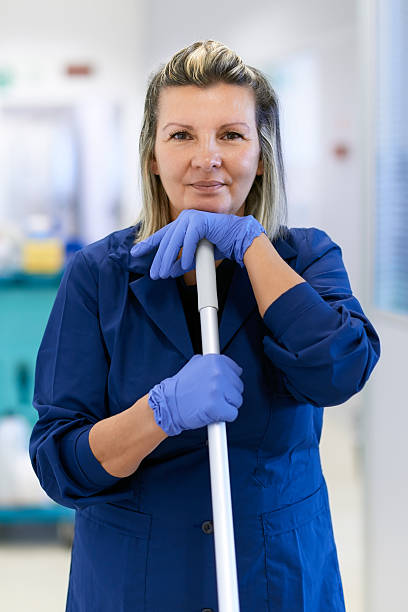 portrait of happy professional female cleaner smiling in office - maid stock pictures, royalty-free photos & images