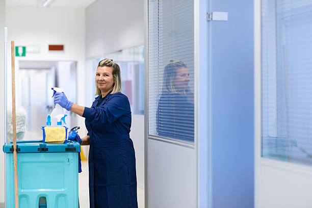 Portrait of happy professional female cleaner smiling in office stock photo