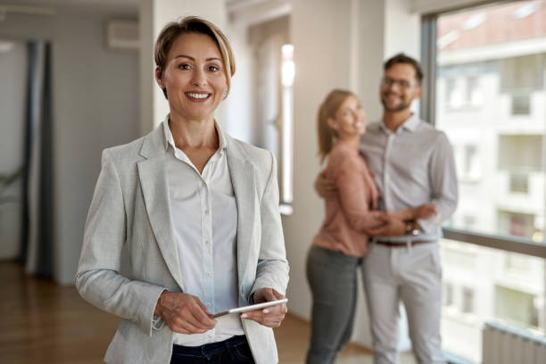 Portrait of happy real estate agent with a couple in the background. stock photo