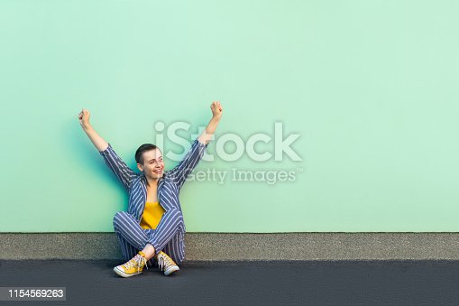 Portrait of happy rejoicing handsome beautiful short hair young woman in casual striped suit sitting and celebrating her victory or success. indoor studio shot isolated on light green background.