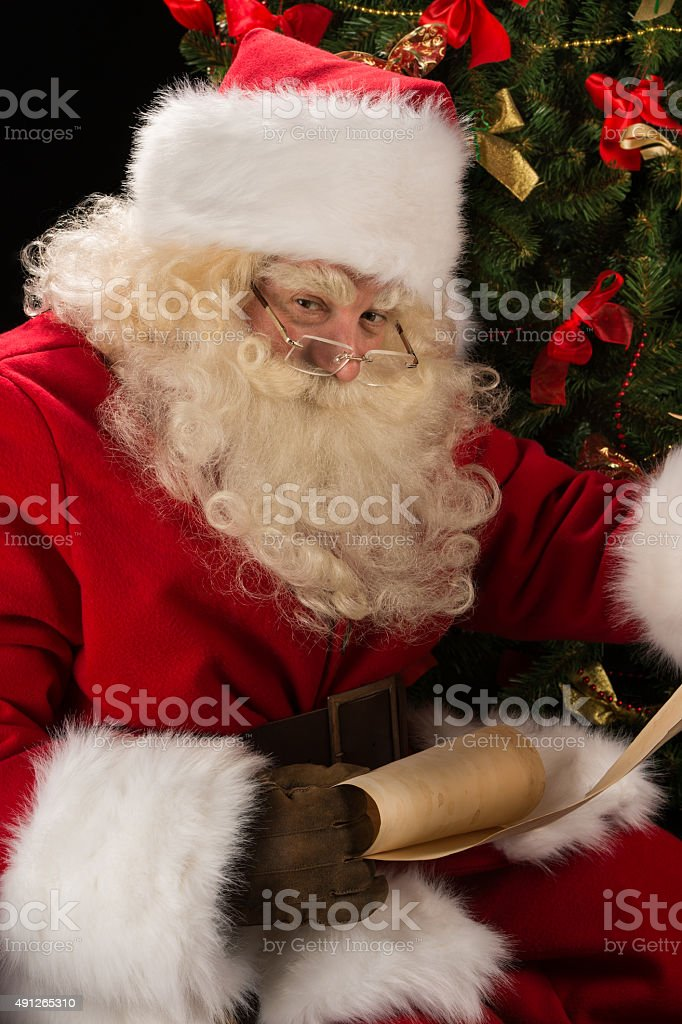 Portrait of happy santa claus reading christmas letter stock photo adult adults only cap christmas event portrait of happy santa claus reading christmas letter spiritdancerdesigns Gallery