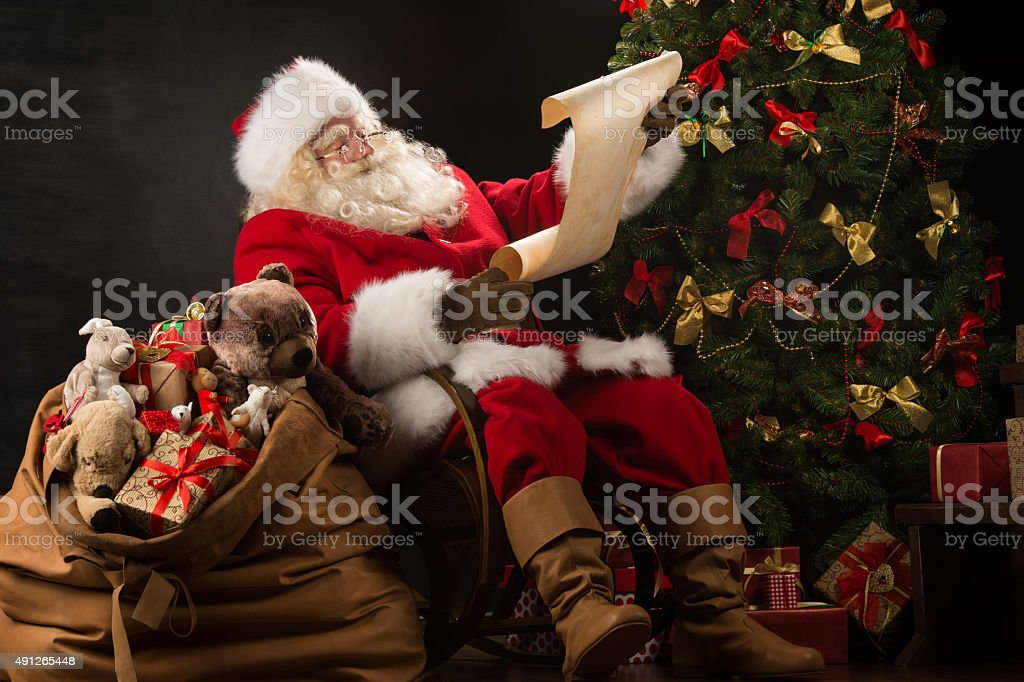Portrait of happy Santa Claus reading Christmas letter stock photo