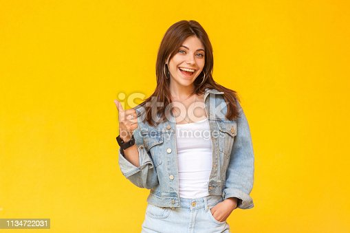istock Portrait of happy satisfied beautiful brunette young woman with makeup in denim casual style standing, thumbs up and looking at camera excited. 1134722031
