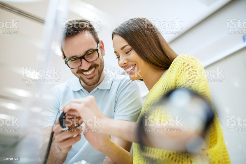 Portrait of happy satisfied smiling young couple in love holding a wristwatch in a tech store. stock photo