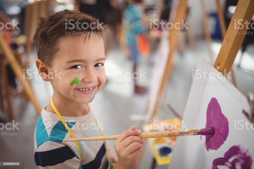 Portrait of happy schoolboy panting on canvas stock photo