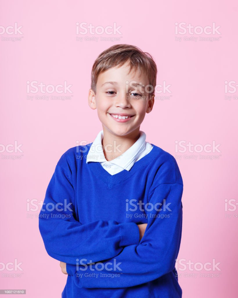 Portrait of happy schoolboy smiling against pink background Happy schoolboy wearing school uniforms standing with arms crossed. Studio shot, pink background. 8-9 Years Stock Photo
