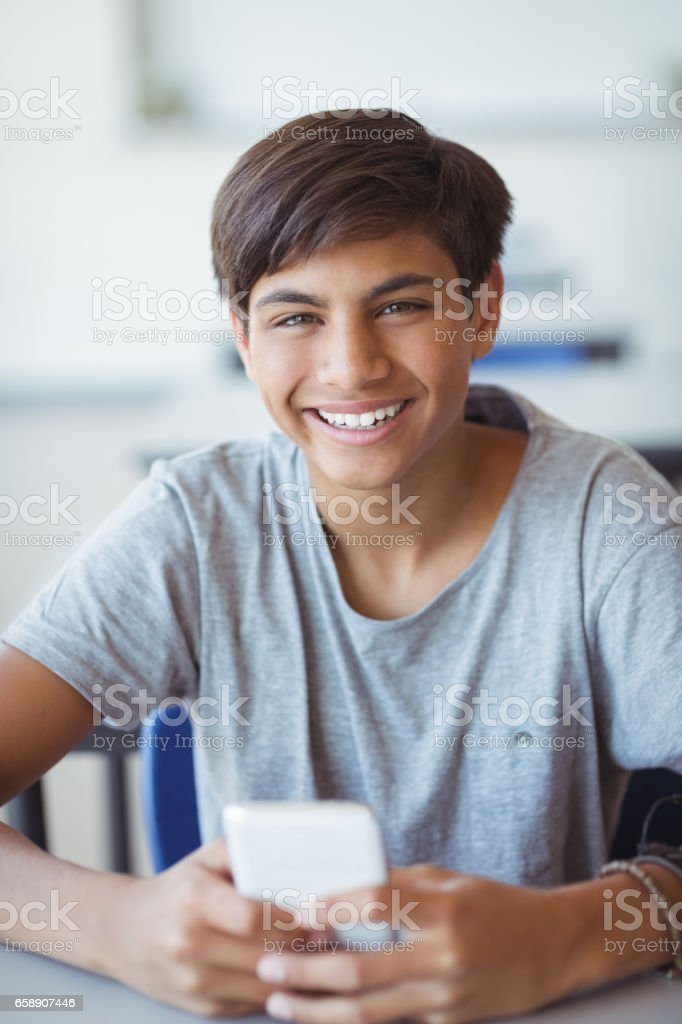 Portrait of happy schoolboy using mobile phone in classroom stock photo