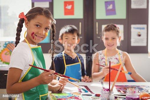 istock Portrait of happy schoolkids practicing drawing 846410324