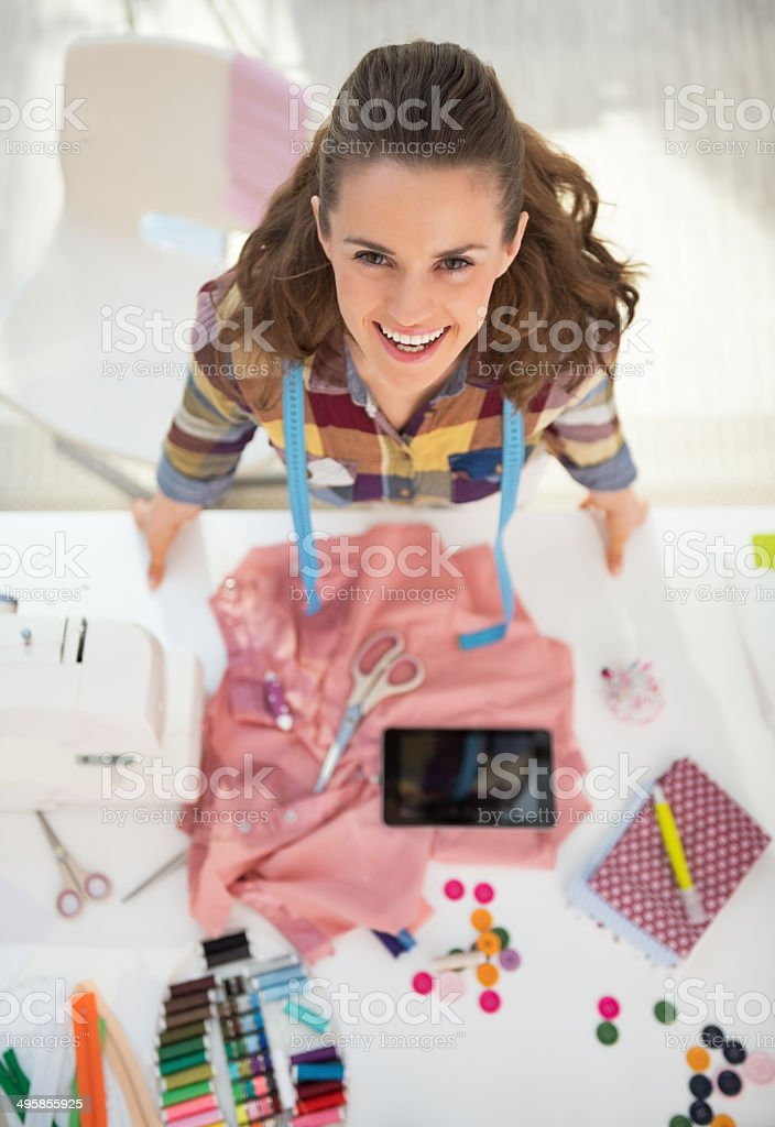 portrait of happy seamstress at work stock photo