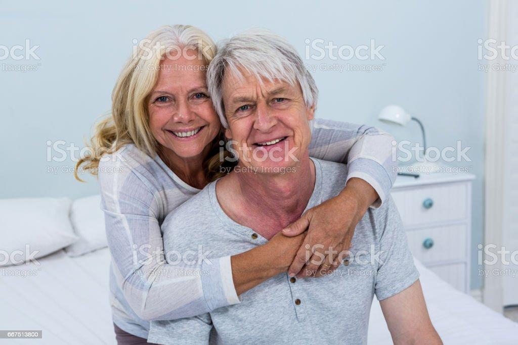 Portrait of happy senior couple hugging in bedroom foto stock royalty-free