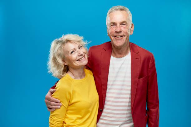 retrato do par sênior feliz com os braços em torno de se - lifestyle color background - fotografias e filmes do acervo