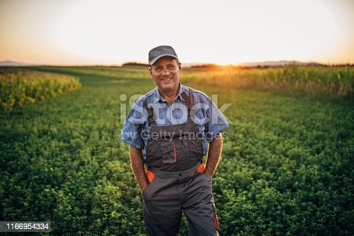 One senior farmer with coveralls and cap standing in field, looking at camera and smiling.