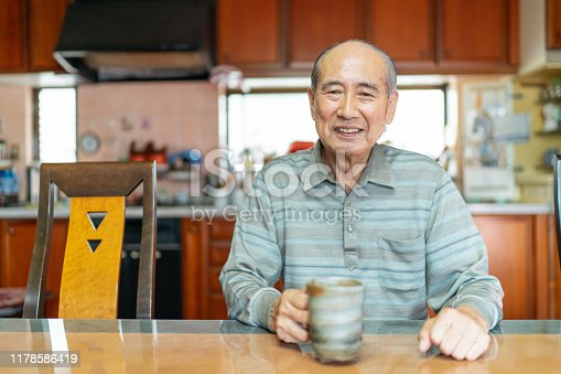 A portrait of a happy senior man while holding a coffee mug at home.