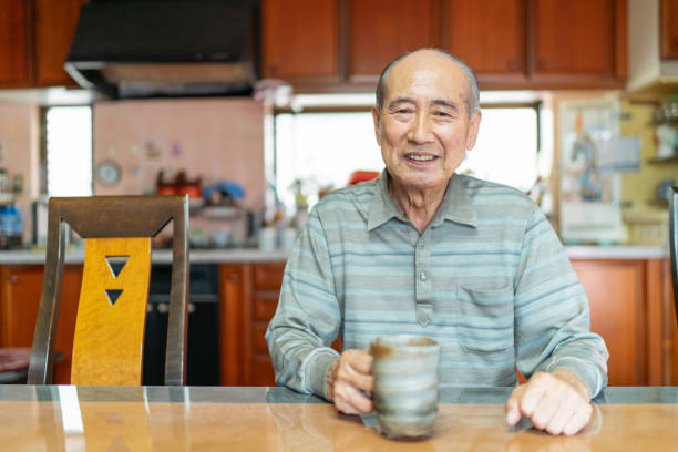 Portrait of happy senior man at home A portrait of a happy senior man while holding a coffee mug at home. east asian culture stock pictures, royalty-free photos & images