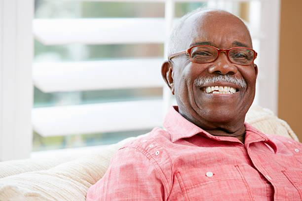 portrait of happy senior man at home - sadece yaşlı bir adam stok fotoğraflar ve resimler