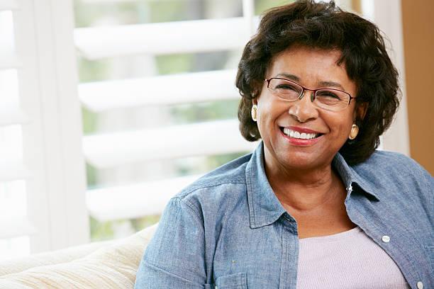 portrait de femme âgée heureuse à la maison - une seule femme senior photos et images de collection
