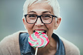 Happy mature woman having fun while eating colorful lollipop and looking at camera.