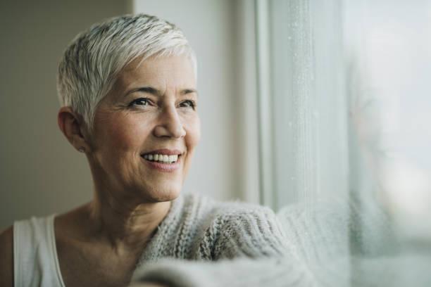 mutlu kadın kıdemli pencerenin kenarında düşleyerek portresi. - doğal poz stok fotoğraflar ve resimler